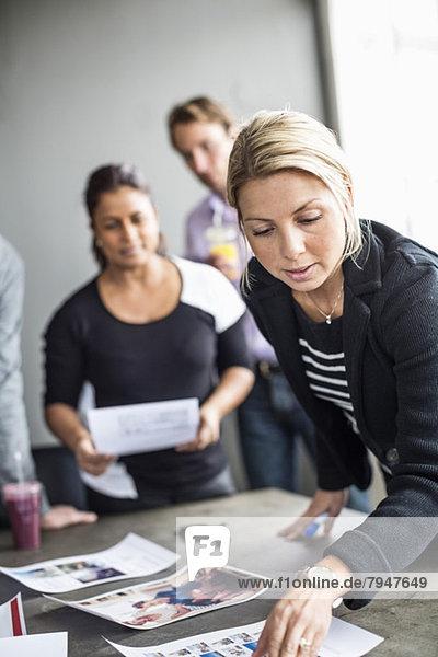 Mittlere erwachsene Geschäftsfrau beim Betrachten von Fotos während der Arbeit mit Kollegen im Büro