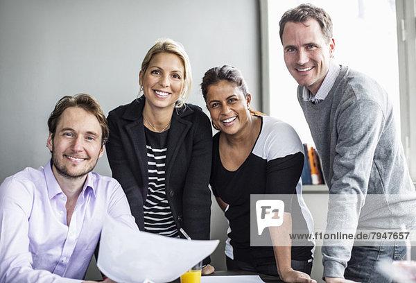 Portrait von glücklichen Geschäftskollegen am Schreibtisch im Büro