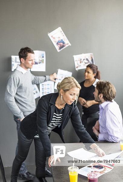 Mittlere erwachsene Geschäftsfrau beim Blick auf Papier am Schreibtisch mit Kollegen  die im Hintergrund diskutieren.