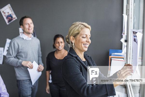 Mittlere erwachsene Geschäftsfrau klebt Papier mit Kollegen im Hintergrund im Büro