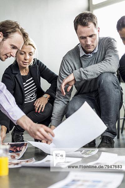 Geschäftskollegen hocken beim Betrachten von Fotos im Büro