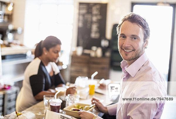 Seitenansicht Porträt eines mittelgroßen Geschäftsmannes beim Frühstück mit Kollegen im Hintergrund im Bürorestaurant Seitenansicht Porträt eines mittelgroßen Geschäftsmannes beim Frühstück mit Kollegen im Hintergrund im Bürorestaurant