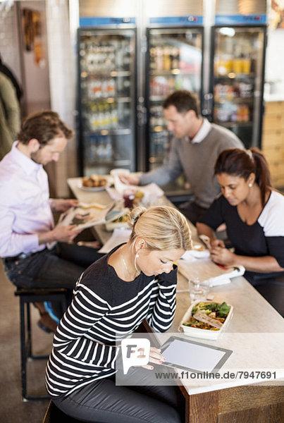 Großer Blickwinkel auf die mittlere erwachsene Geschäftsfrau mit digitalem Tablett und Kollegen im Hintergrund am Bürorestauranttisch