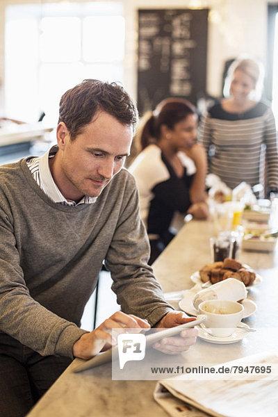 Geschäftsmann mit digitalem Tablett am Tisch mit weiblichen Kollegen im Hintergrund