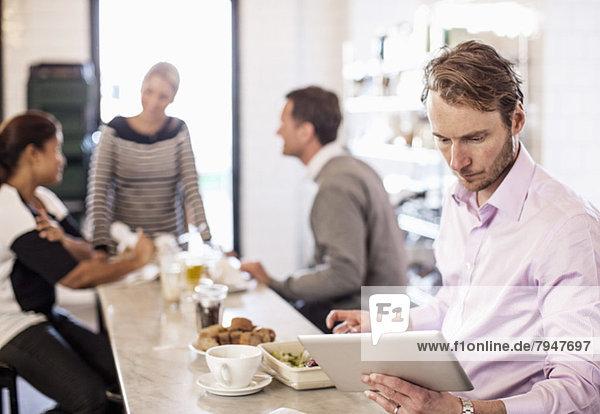 Mittlerer erwachsener Geschäftsmann mit digitalem Tablett am Restauranttisch mit Geschäftskollegen im Hintergrund