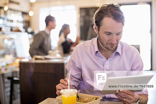 Mittlerer erwachsener Geschäftsmann  der sich beim Frühstück am Tisch im Restaurant ein digitales Tablett ansieht.