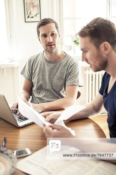 Homosexuell Mann mit Laptop  während Freund Lesung Papier am Tisch zu Hause