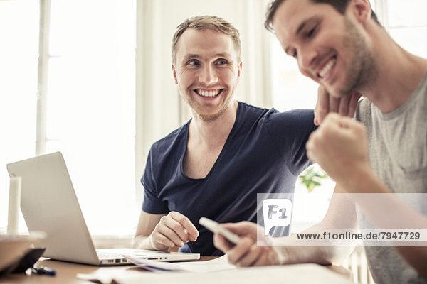 Fröhliches homosexuelles Paar mit Laptop am Tisch zu Hause