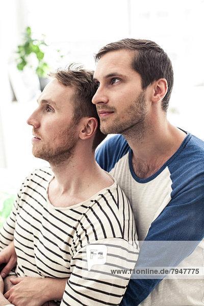 Nachdenkliches junges homosexuelles Paar schaut weg  während es sich zu Hause umarmt.