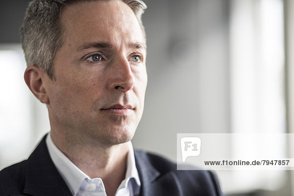 Pensive mature businessman looking away in office