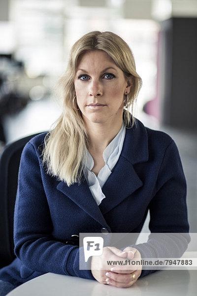Porträt einer selbstbewussten mittelständischen Unternehmerin am Schreibtisch im Büro
