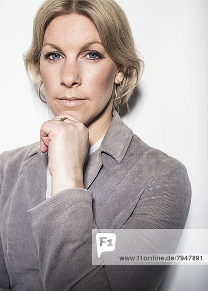 Portrait of businesswoman standing with hand on chin against wall