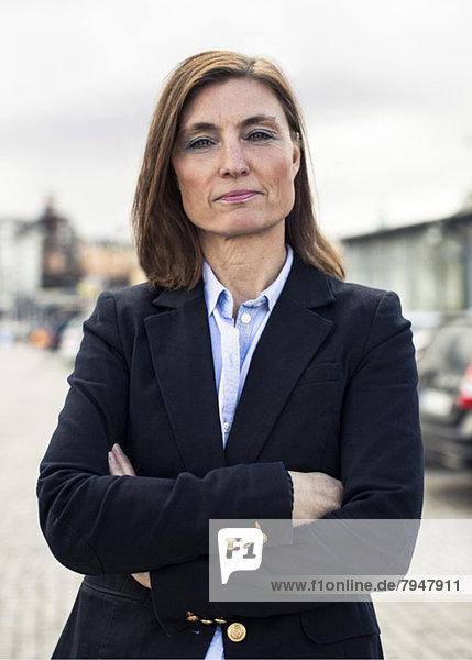 Porträt einer selbstbewussten  reifen Geschäftsfrau  die auf der Straße steht.