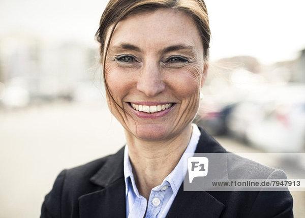 Porträt einer fröhlichen  reifen Geschäftsfrau  die im Freien lächelt.