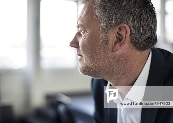 Close-up of mature businessman looking away in office