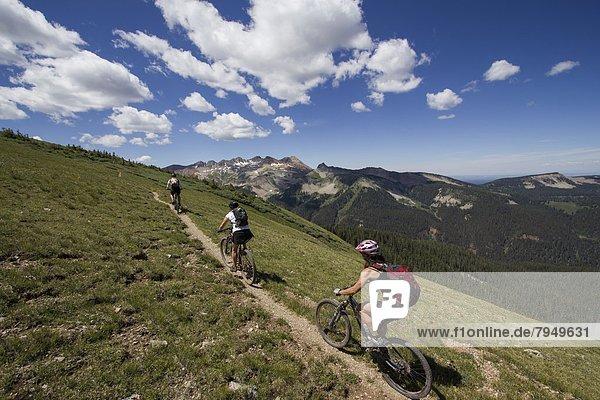 Three mountain bikers riding on a trail through the mountains.
