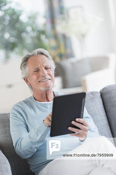 sitzend  Senior  Senioren  Mann  Couch  Tablet PC