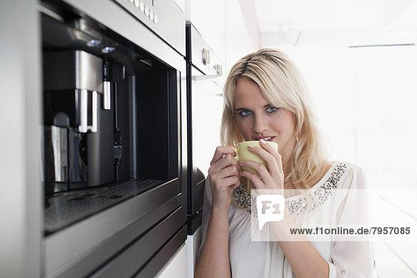 Frau trinkt Kaffee in Küche