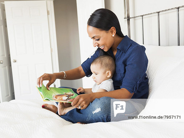 Mother showing her son (2-5 months) book and reading