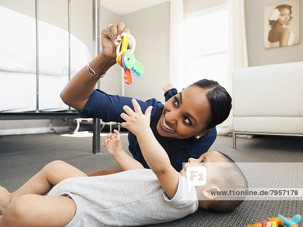Mother playing with her son (2-5 months) on the floor of living room