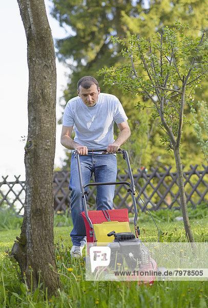 Mittlerer Erwachsener Mann im Garten mit Rasenmäher