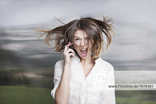 Junge Frau schreit am Telefon