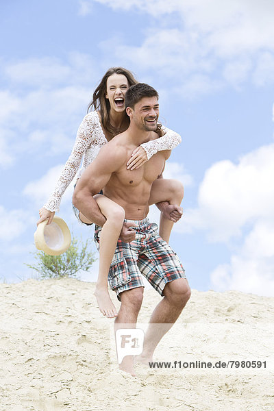 Junger Mann reitet Huckepack zu Frau