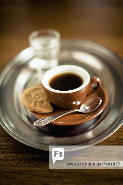 Espresso schwarzer Kaffee mit Keks und Glas Wasser auf dem Tablett
