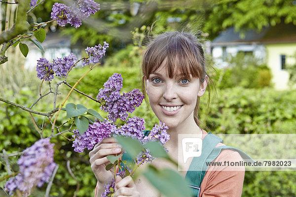 Porträt einer jungen Frau mit fliederfarbenen Blumen  lächelnd