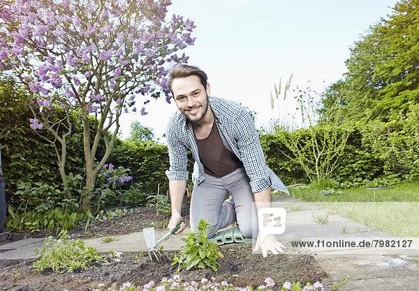 Porträt eines jungen Mannes im Garten  lächelnd