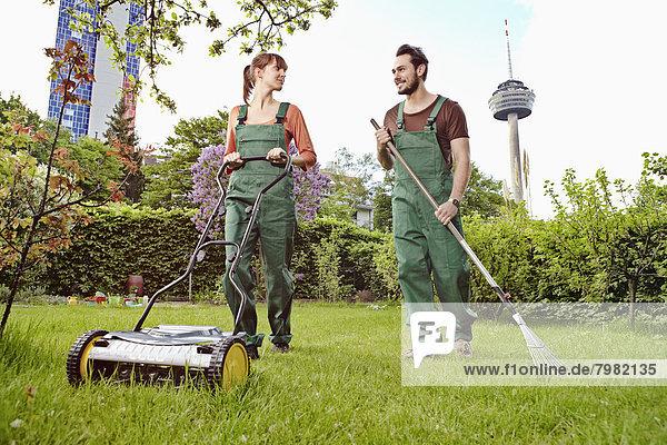 Deutschland  Köln  Junges Paar Gartenarbeit  lächelnd
