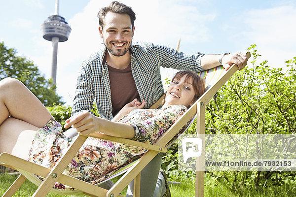 Deutschland  Köln  Junges Paar entspannt im Garten  lächelnd