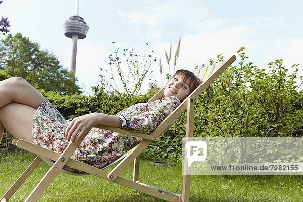 Porträt einer jungen Frau  die sich auf dem Liegestuhl im Garten entspannt  lächelnd