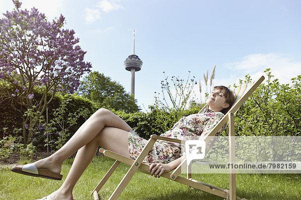 Junge Frau entspannt auf Liegestuhl im Garten