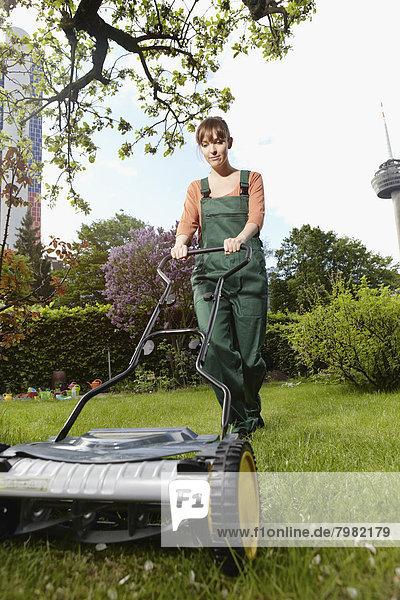 Junge Frau mäht Rasen mit Schubmäher
