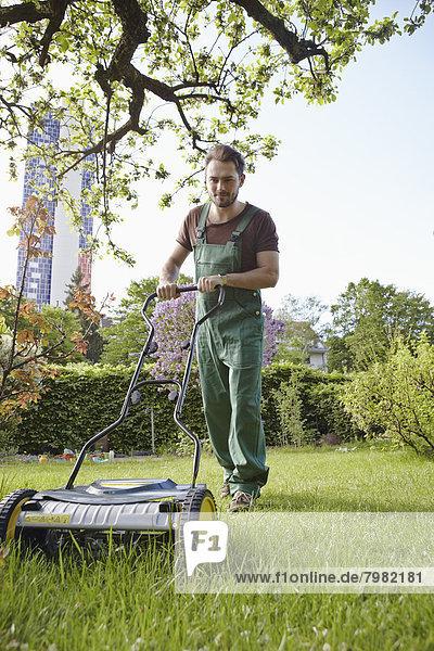 Junger Mann mäht Rasen mit Schubmäher