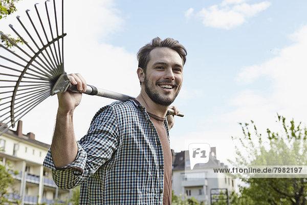Porträt eines jungen Mannes mit Rechen  lächelnd