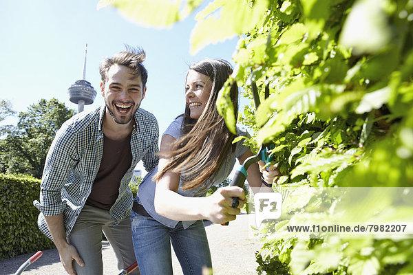 Deutschland  Köln  Junges Paar  das mit einer Schere Blätter schneidet  lächelt
