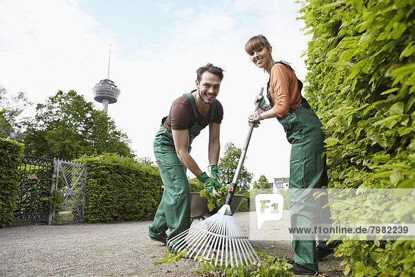 Deutschland  Köln  Junges Paar  lächelndes Laub rechend