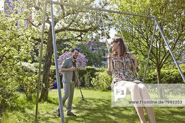 Junge Frau schwingt,  während der Mann den Rasen im Hintergrund reibt.