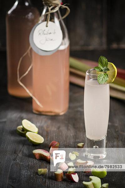 Glas Rhabarber mit Rhabarbersaftflasche und Rhabarberstücken auf Holztisch  Nahaufnahme