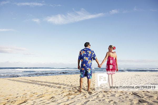 USA  Hawaii  Mid adult couple walking on beach
