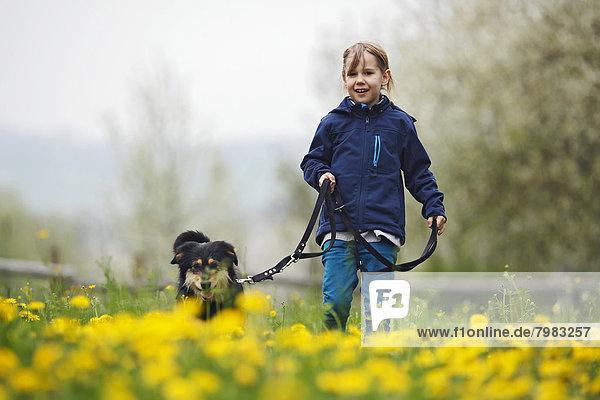 Deutschland  Baden Württemberg  Porträt eines Mädchens mit Hund auf der Wiese