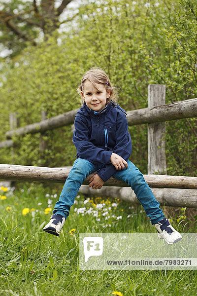 Deutschland  Baden Württemberg  Portrait eines Mädchens auf dem Zaun sitzend  lächelnd