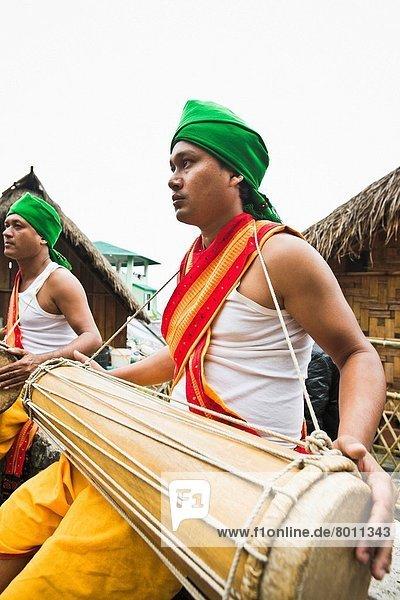Naga tribal men playing musical instrument  Hornbill Festival  Kohima  Nagaland  India