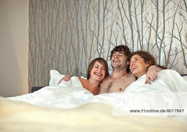 Junger Mann im Bett mit zwei jungen Frauen