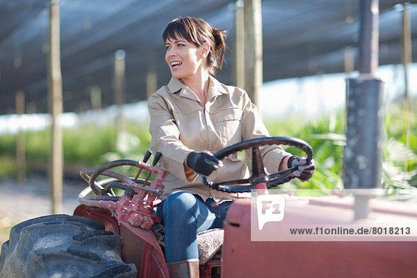 Frau auf dem Fahrzeug in der Gärtnerei