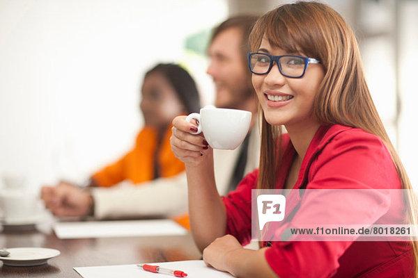 Junge Frau mit Kaffee lächelnd in Richtung Kamera