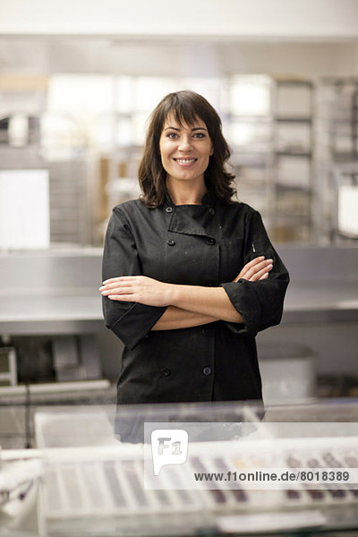 Portrait of woman in commercial kitchen with arms folded
