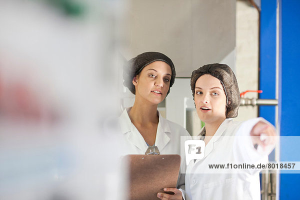 Two women working in olive processing plant